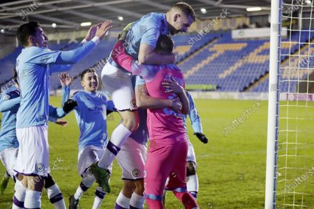 Stock Photo of Manchester City players celebrate victory in the penalty shoot out as they congratulate goalkeeper Daniel Grimshaw