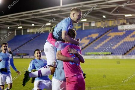 Manchester City players celebrate victory in the penalty shoot out as they congratulate goalkeeper Daniel Grimshaw