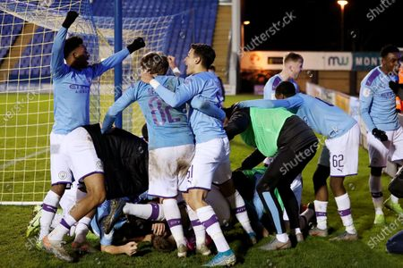Stock Image of Manchester City players celebrate victory in the penalty shoot out as they congratulate goalkeeper Daniel Grimshaw