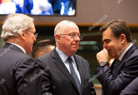 European Commissioner for Promoting our European Way of Life Margaritas Schinas, right, speaks with Ireland's Interior Minister Charles Flanagan, center, during a meeting of EU Interior ministers at the EU Council building in Brussels