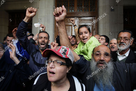 People react outside the courtroom as two former Algerian prime ministers, Ahmed Ouyahia and Abdelmalek Sellal, go on trial on corruption charges in a much-awaited public trial amid a protest movement seeking to push out the powers-that-be, Monday Dec.2, 2019 in Algiers