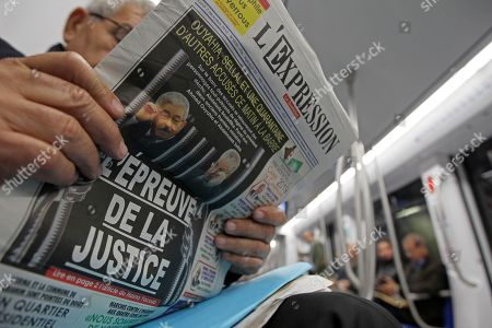 A man reads a newspaper headlining on the trial of two former Algerian prime ministers, Ahmed Ouyahia and Abdelmalek Sellal, Monday Dec.2, 2019 in Algiers. Ahmed Ouyahia and Abdelmalek Sellal go on trial on corruption charges in a much-awaited public trial amid a protest movement seeking to push out the powers-that-be