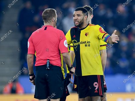 Troy Deeney of Watford argues with referee Craig Pawson after a penalty was awarded to Leicester City