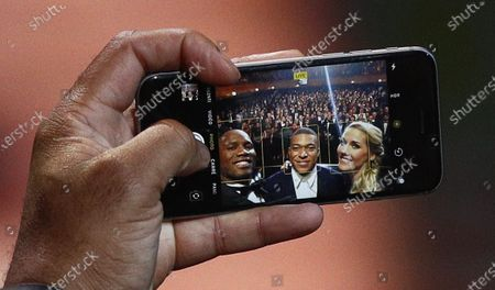 Hosts of the Ballon d'Or ceremony Sandy Heribert (R) and Didier Drogba take a selfie with the 2018 Kopa Trophy winner Kylian Mbappe (C) during the show at the Theatre du Chatelet in Paris, France, 02 December 2019.