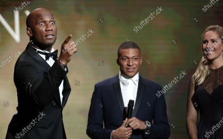 Hosts of the Ballon d'Or ceremony Sandy Heribert (R) and Didier Drogba and the 2018 Kopa Trophy winner Kylian Mbappe (C) during the show at the Theatre du Chatelet in Paris, France, 02 December 2019.