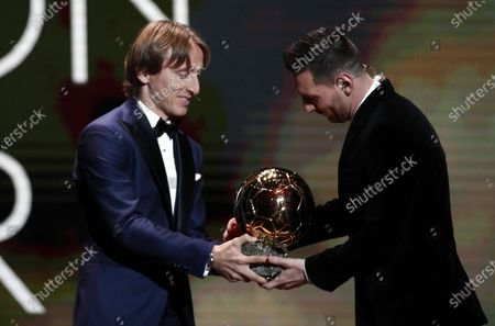 Barcelona forward Lionel Messi (R) wins the Men's 2019 Ballon d'Or and receives the award from the 2018 winner Luka Modric at the Ballon d'Or ceremony at Theatre du Chatelet in Paris, France, 02 December 2019.