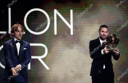Stock Picture of Barcelona forward Lionel Messi (R) poses with the Men's 2019 Ballon d'Or after receiving the award from the 2018 winner Luka Modric (L) at the Ballon d'Or ceremony at Theatre du Chatelet in Paris, France, 02 December 2019.