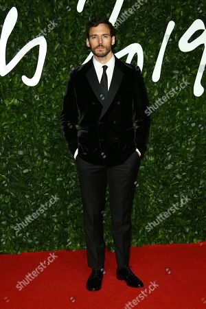 Sam Claflin poses for photographers upon arrival at the British Fashion Awards in central London