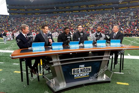Fox Sports host Rob Stone, from left, and analysts Brady Quinn, Reggie Bush, Matt Leinart, Heisman Trophy winner Charles Woodson and former Ohio State coach Urban Meyer appear before an NCAA college football game between Michigan and Ohio State in Ann Arbor, Mich