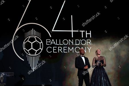 Former soccer player Didier Drogba, left, and Sandy Heribert presenters of the Golden Ball award ceremony speak at the Grand Palais in Paris,. Awarded every year by France Football magazine since Stanley Matthews won it in 1956, the Ballon d'Or, Golden Ball for the best player of the year will be given to both a woman and a man