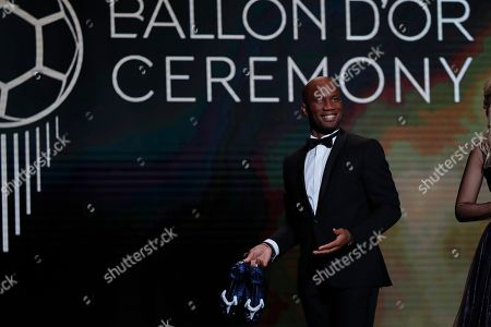 Former soccer star Didier Drogba and presenter of the Golden Ball award ceremony holds soccer shoes at the Grand Palais in Paris,. Awarded every year by France Football magazine since Stanley Matthews won it in 1956, the Ballon d'Or, Golden Ball for the best player of the year will be given to both a woman and a man