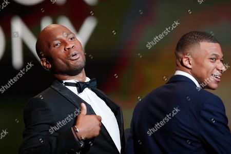Former soccer star Didier Drogba and presenter, left, of the Golden Ball award ceremony jokes as Paris Saint Germain's Kylian Mbappe laughs at the Grand Palais in Paris,. Awarded every year by France Football magazine since Stanley Matthews won it in 1956, the Ballon d'Or, Golden Ball for the best player of the year will be given to both a woman and a man