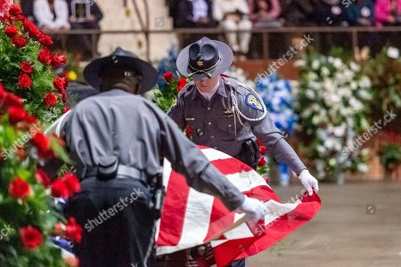 """A U.S. flag is placed on the casket during the memorial service for slain Lowndes County Sheriff """"Big John"""" Williams, in Montgomery, Ala"""