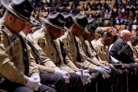 """Deputies from the Lowndes County Sheriff's department bow their heads in prayer during the eulogy at the memorial service for slain Lowndes County Sheriff """"Big John"""" Williams, in Montgomery, Ala"""