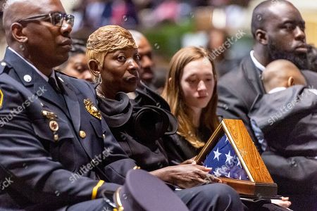 """Joann Williams holds the U.S. flag that flew over the Capitol to honor her husband, during the memorial service for slain Lowndes County Sheriff """"Big John"""" Williams, in Montgomery, Ala"""