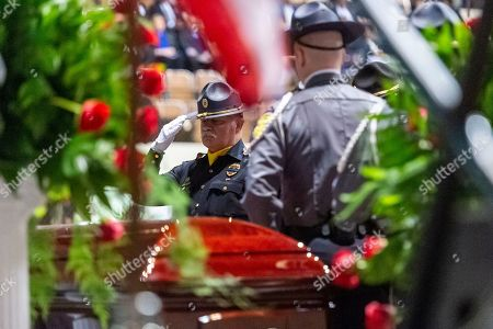 """The casket is saluted before being draped in a U.S. flag during the memorial service for slain Lowndes County Sheriff """"Big John"""" Williams, in Montgomery, Ala"""