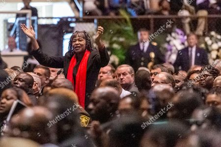 """A mourner stands and claps as music plays during the memorial service for slain Lowndes County Sheriff """"Big John"""" Williams, in Montgomery, Ala"""