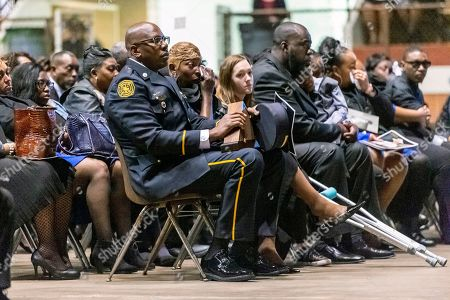 """Joann Williams, center, wipes away tears as the 'end of watch' is dispatched over the air, ending the memorial service for her husband, slain Lowndes County Sheriff """"Big John"""" Williams, in Montgomery, Ala"""