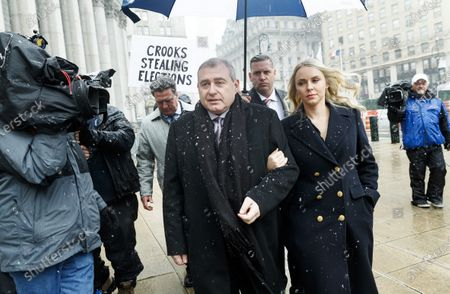Businessman Lev Parnas (C), an associate of US President Donald Trump's personal lawyer, Rudy Giuliani, walks with his wife Svetlana (R) and his legal team as a protestor holds a sign while arriving for a hearing at an United States Federal Courthouse in New York, New York, USA, 02 December 2019. Parnas, and another man, Igor Fruman, were arrested on 10 October 2019 for alleged campaign finance violations.