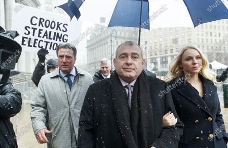Stock Photo of Businessman Lev Parnas (C), an associate of US President Donald Trump's personal lawyer, Rudy Giuliani, walks with his wife Svetlana (R) and his legal team as a protestor holds a sign while arriving for a hearing at an United States Federal Courthouse in New York, New York, USA, 02 December 2019. Parnas, and another man, Igor Fruman, were arrested on 10 October 2019 for alleged campaign finance violations.
