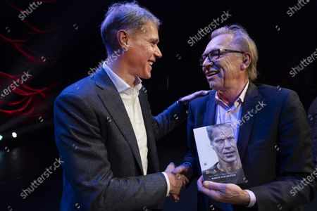 Dutch soccer legend Marco van Basten (L) receives the first copy of his BASTA biography from Jan Mulder (R) at the Amsterdam International Theater, Amsterdam, The Netherlands, 02 December 2019.