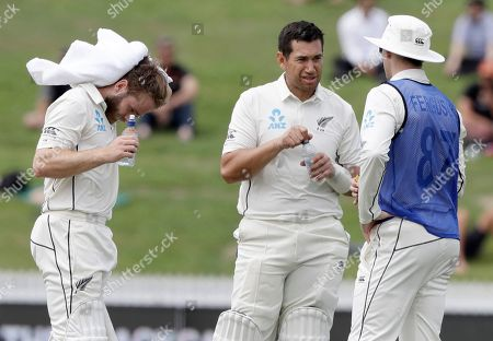 New Zealand's Kane Williamson, left, and batting partner Ross Taylor take a drinks break with teammate Lockie Ferguson, right, during play on the final day of the second cricket test between England and New Zealand at Seddon Park in Hamilton, New Zealand