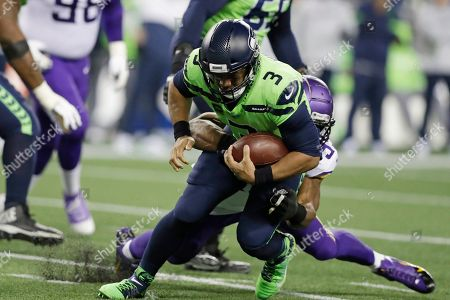 Seattle Seahawks quarterback Russell Wilson (3) is brought down by Minnesota Vikings' Danielle Hunter during the first half of an NFL football game, in Seattle