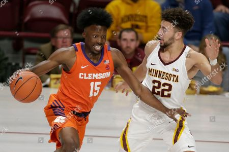 Clemson forward John Newman III (15) drives against Minnesota guard Gabe Kalscheur (22) in the first half during an NCAA basketball game, in Minneapolis