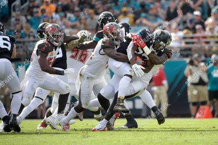 Stock Photo of Jacksonville Jaguars running back Leonard Fournette (27) is stopped behind the line of scrimmage on a running play by Tampa Bay Buccaneers linebacker Devin White and linebacker Jason Pierre-Paul, right, during the first half of an NFL football game, in Jacksonville, Fla