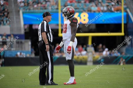 Official Tom Stephan (68) talks with Tampa Bay Buccaneers linebacker Jason Pierre-Paul (90) during the first half of an NFL football game against the Jacksonville Jaguars, in Jacksonville, Fla