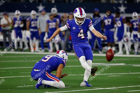 Buffalo Bills' Corey Bojorquez (9) holds as place kicker Stephen Hauschka (4) kicks the ball during an NFL football game against the Dallas Cowboys in Arlington, Texas