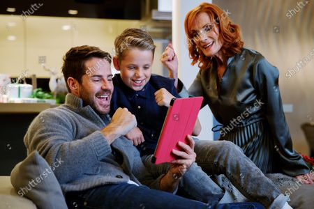 Stock Image of Jamie Redknapp, mother Sandra Redknapp and son test out a new game from Vodafone's reward scheme