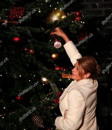 Desislava, the wife of Bulgarian President Rumen Radev places a bauble on a Christmas tree as they arrive at 10 Downing Street in London ahead of a NATO reception hosted by British Prime Minister Boris Johnson, . U.S. President Donald Trump and his NATO counterparts were gathering in London Tuesday to mark the alliance's 70th birthday amid deep tensions as spats between leaders expose a lack of unity that risks undermining military organization's credibility