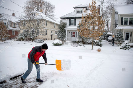 Paul Mooney shovels snow outside his home, in Providence, R.I