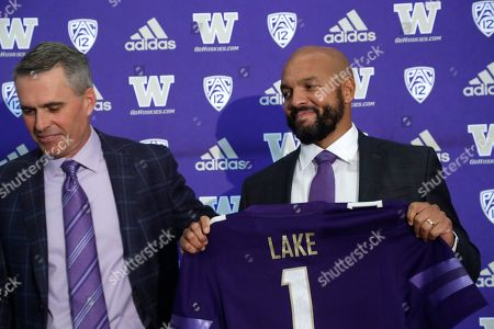 Washington football defensive coordinator Jimmy Lake, right, poses for a photo as head coach Chris Petersen steps aside following a news conference about Lake taking over the head coaching position, in Seattle. Petersen unexpectedly resigned at Washington on Monday, a shocking announcement with the Huskies coming off a 7-5 regular season and bound for a sixth straight bowl game under his leadership. Petersen will coach Washington in a bowl game, his final game in charge