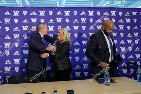 Washington football head coach Chris Petersen, left, is embraced by athletic director Jen Cohen as defensive coordinator Jimmy Lake steps aside after a news conference about Petersen's decision to resign and Lake taking over his job, in Seattle. Petersen unexpectedly resigned at Washington on Monday, a shocking announcement with the Huskies coming off a 7-5 regular season and bound for a sixth straight bowl game under his leadership. Petersen will coach Washington in a bowl game, his final game in charge