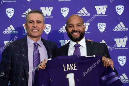Washington football defensive coordinator Jimmy Lake, right, poses for a photo with head coach Chris Petersen following a news conference about Lake taking over the head coaching position, in Seattle. Petersen unexpectedly resigned at Washington on Monday, a shocking announcement with the Huskies coming off a 7-5 regular season and bound for a sixth straight bowl game under his leadership. Petersen will coach Washington in a bowl game, his final game in charge