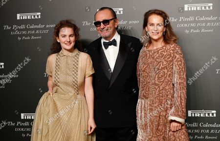 Italian photographer Paolo Roversi, center, poses with his wife and his daughter Stella, left, at the 2020 Pirelli Calendar event in Verona, Italy