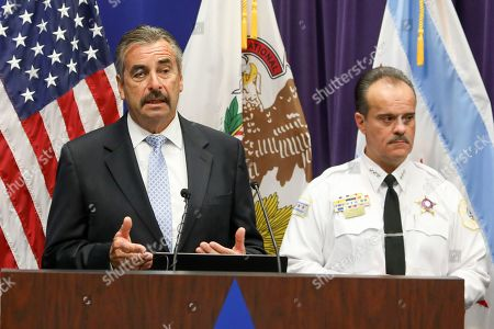 Former Los Angeles Police Chief Charlie Beck, left, who was named interim police superintendent in Chicago by Mayor Lori Lightfoot, addresses a news conference where he fielded questions on the firing by Lightfoot of retiring superintendent Eddie Johnson and Facebook gun sales . Standing with Beck is First Deputy Superintendent Anthony Riccio, as the pair announced that investigators have arrested more than 50 people accused of using private Facebook groups and messages to sell guns or drugs. Police also blamed the social media company for complicating such cases by taking down investigators' fake profiles during a Tuesday press conference announcing results of the two-year investigation