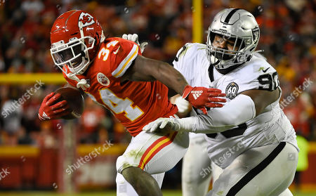 Kansas City Chiefs running back Darwin Thompson (34) is pushed out of bounds by Oakland Raiders defensive tackle Johnathan Hankins (90) during the second half of an NFL football game in Kansas City, Mo