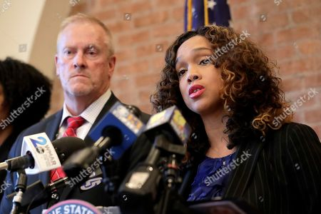 Maryland corrections secretary Robert Green, left, listens as Maryland State Attorney Marilyn Mosby, right, speaks during a news conference announcing the indictment of correctional officers, in Baltimore. Twenty five correction officers, most of whom were taken into custody earlier in the day, are charged with using excessive force on detainees at state-operated Baltimore pretrial correctional facilities