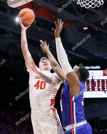Stock Photo of Chase Johnson, Zach Iyeyemi. Dayton's Chase Johnson (40) shoots against Houston Baptist's Zach Iyeyemi (34) during the first half of an NCAA college basketball game, in Dayton, Ohio