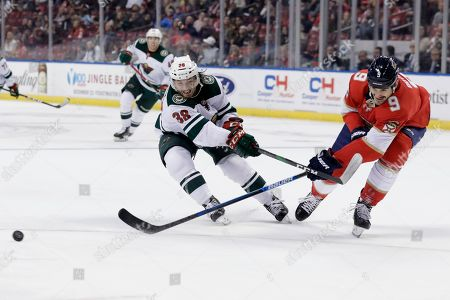 Ryan Hartman, Brian Boyle. Minnesota Wild right wing Ryan Hartman (38) and Florida Panthers center Brian Boyle (9) chase the puck during the second period of an NHL hockey game, in Sunrise, Fla