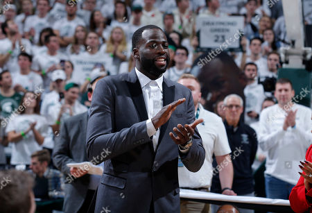 Stock Picture of Former Michigan State and current Golden State Warriors player Draymond Green applauds during a ceremony in which his Michigan State jersey number was retired, at halftime of an NCAA college basketball game between Michigan State and Duke, in East Lansing, Mich