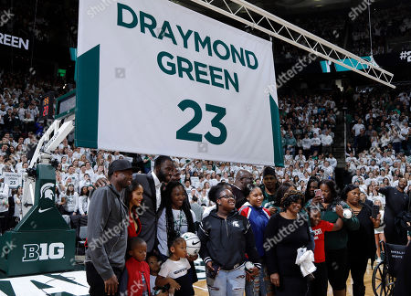 Former Michigan State and current Golden State Warriors player Draymond Green stands with family members during a ceremony in which his jersey number was retired, at halftime of an NCAA college basketball game between Michigan State and Duke, in East Lansing, Mich