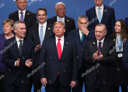 NATO leaders from front left, German Chancellor Angela Merkel, NATO Secretary General Jens Stoltenberg, U.S. President Donald Trump, Hungarian Prime Minister Viktor Orban, Turkish President Recep Tayyip Erdogan and Iceland's Prime Minister Katrin Jakobsdottir attend a ceremony event during a NATO leaders meeting at The Grove hotel and resort in Watford, Hertfordshire, England, . NATO Secretary-General Jens Stoltenberg rejected Wednesday French criticism that the military alliance is suffering from brain death, and insisted that the organization is adapting to modern challenges