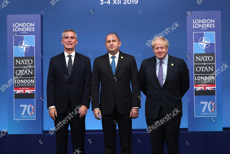 NATO Secretary General Jens Stoltenberg, left, and British Prime Minister Boris Johnson, right, welcome Bulgarian President Rumen Radev at official arrivals for a NATO leaders meeting at The Grove hotel and resort in Watford, Hertfordshire, England, . NATO Secretary-General Jens Stoltenberg rejected Wednesday French criticism that the military alliance is suffering from brain death, and insisted that the organization is adapting to modern challenges