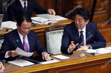 Japanese Prime Minister Shinzo Abe (R) chats with Finance Minister Taro Aso (L) before starting Upper House's plenary session