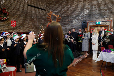 Stock Photo of First lady Melania Trump and Suzanne Johnson, wife of the US ambassador to Britain, 4th right, listen to a children choir after joining local students wrapping holiday presents to be donated to the Salvation Army, at the Salvation Army Clapton Center in London
