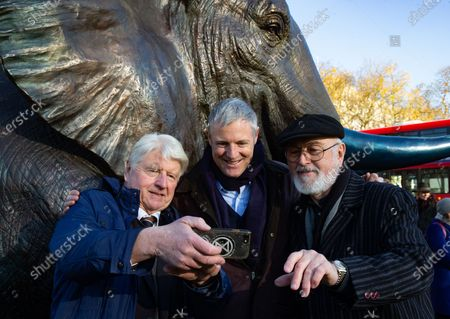 Stock Picture of Environmentalist and Author, Stanley Johnson takes a selfie with Zac Goldsmith, Minister for Environmenmt, Food and Rural Affairs with Downton Abbey actor, Peter Egan, supporting the launch. The sculptures are by Artists ,Gillie and Marc.21 Bronze Life-sized Elephants unveiled at Marble Arch to hight the plight of the species which faces extinction by 2040.